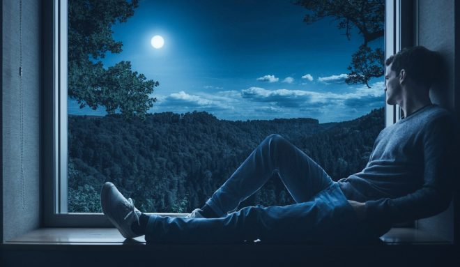мужчина смотрит в окно на луну